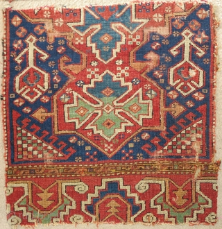 "Two fragments of an exceptional 18th century blue-ground Bergama area rug with a curled tendril palmette border. Each approximately 2'6""x2'6""."