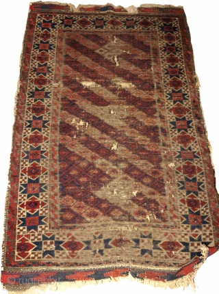 worn antique Khorosan Baluch rug with great star border. Diagonal stripes with a pile rendition of flatweave design. corrosive browns.