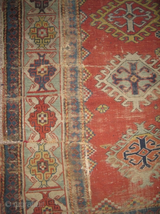 "Kazak Rug, Old, Colorful with a Kufic border. Several blues and greens, two natural oranges, great aubergine highlights. In ""as found"" condition. browns are corroded and there are several rips or rather  ..."
