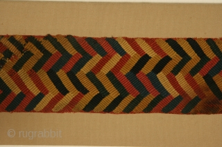 Belt fragment, Paracas Ocucaje culture, Peru, plaited camelid wool, circa 300-100 BC, actual piece is 4 x 30 inches, mounted dimensions are 7 x 33 inches.