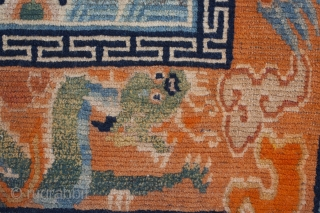 Charming Tibetan sitting rug depicting a snow lion. Dragon border. Lovely animals with great features. Typical signs of wear for a saddle top rug. Circa 1920. 70*57cm.
