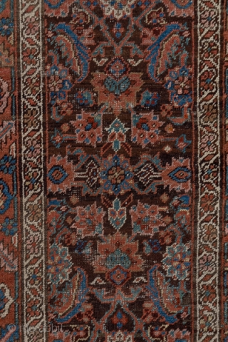 Heriz Runner  2.6 x 17.4 0.79 x 5.30   The abrashed dark brown field displays a single column Herati design detailed in ivory, medium blue, terra cotta and green. The Herati diamonds are all concave  ...