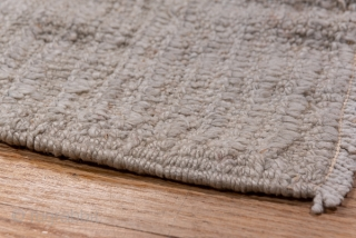 Tulu Mansion Carpet  13.9 by 23.1 4.23 x 7.04   This oversize central Anatolian village carpet is very coarse woven with  multiple wefts, recumbent, long pile and a flattish surface of uniformly oatmeal colour.  ...