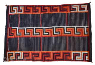 A gorgeous Navajo Transitional blanket (1880-1910) tightly woven in handspun native wool, in natural brown and ivory, indigo and aniline colors, with a variant Chief's design, c1880.