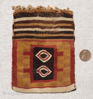 This small, finely woven Incan period tapestry bag has different designs on each face. It has a subtle checkerboard background with two coca leaf motifs or eye symbols worked in eccentric wefts  ...