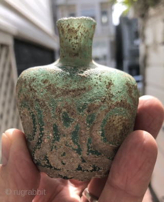 Jade green, thick walled Sassanian glass bottle.  Ancient Near East/Central Asia, Sassanid Empire.  Probably 5th century A.D.  Size: 3.25 x 2.50 inches. Deeply cut faceted design.  Typical pearlescent  ...