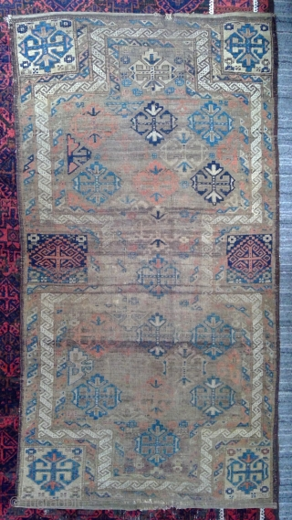 Antique Symmetrically knotted Baluch Double-ended prayer rug with rare design. 34.5 x 62 inches. Mostly even low pile with heavily corroded brown areas. Original sides and kilim ends