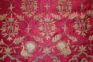 A beautiful full-length Ghaghra (skirt) cloth from Kutch, Gujarat.  The red satin silk Ghaghra is decorated with floral motifs as well as peacocks and female figures under arches at the hem. The border  ...