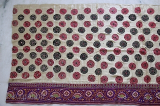 A full-sized embroidered cloth for a Chaniya (Skirt) from Kutch, Gujarat. The cloth is decorated with round flowers and the border with a colourful floral pattern all through the length of the  ...