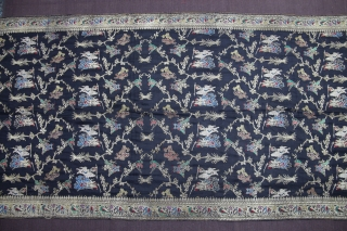A black silk Dupatta decorated with Zari depicting birds perched on trees, tigers hunting deers, peacocks and peahens and warriors fighting on horseback and elephant back. The border, in turn, is decorated  ...