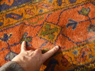 Old Oushak carpet. Over 95% full pile. Age-related wear, minor damage consistent with a roughly hundred year old antique. A couple of ragged areas at the outer border. There are a few,  ...