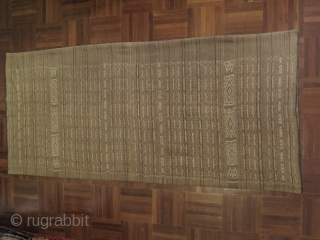 a long tube skirt from Flores Island area, Indonesia. All handspun cotton and vegetable dyes in a yellowish brown interspaced with small horizonal strips of indigo and darker brown tone-on-tone and abstract  ...