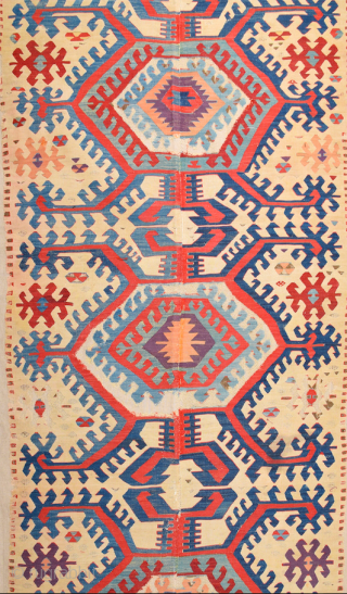 This impressive white-ground kilim is a weaving of the Hotamis Turkmen of the Konya region. It is woven in one piece, so unlike the two-panel kilims of this group there is no  ...