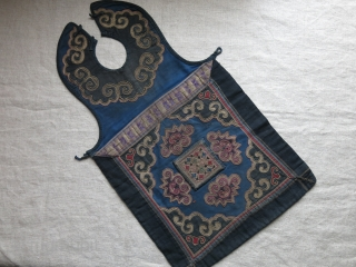CHINESE minority child's apron, pieced out of various natural indigo dyed canvas like cotton fabrics. Tiny transparent wires wrapped and embroidered with silk yarns. Traditional Chinese motifs. Used but still in pretty  ...
