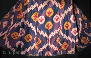Uzbekistan shoi silk ikat chapan. Lining has Russian block print fabric and silk ikat.  Size: Arms spread out 57″ – 146 cm, Height 49″ -126 cm, skirt 36″ – 92 cm.