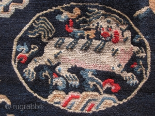 "Tibetan: A pair of large mats, 32 by 36 inches, with prancing and naively drawn central snow lions surrounded by the ""three Fruits"" and a symbol of scholarly accomplishment. c.1930"