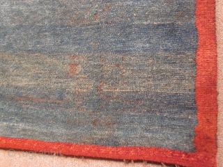 Tibetan, small khaden with abrashed blue green ground, with eccentric red border, 29 by 44 inches, pre-1900