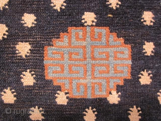 """Tibetan: Small khaden, 27 by 52 inches, field of """"frogs feet"""" with central medallion on deep blue ground. Some re-weaves  c.1900"""