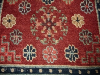 an antique tibetan khaden in superb condition. multicolored lotus flower on a fantastic red background color, beautiful red green border, superb wool and unusual medaillion drawing. the slightly white spot visible on  ...
