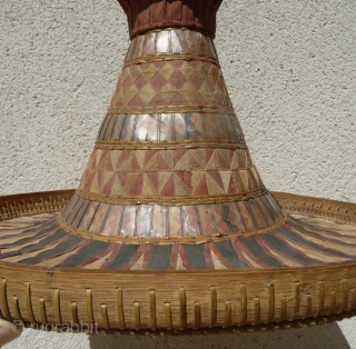 this is a beautiful and rare antique indonesian hat from the south sulawesi. it is made of palm leaves, decorated with pieced cloth and embroidery.the round base is perhaps bambu. please note  ...