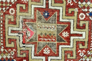 Kazak, Moghan area, 1880's.  Five octagons with Memling Guls and stars of Salomon.  Zoroastic Shamdan Mashaal borders with white ground.  And granulated borders.  Corroding in the black color.  worn with old repairs.  ...