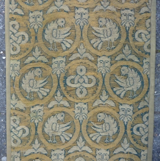 "A long and narrow textile panel, 264  x 73 cm., 8'7"" x 2'5"", with a repeat of circular medallions enclosing birds or endless knots is interspersed with satyr's masks and leaves  ..."