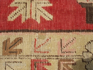 """This circa 1920 Khotan antique carpet measures 4'11"""" x 8'1"""". It has four standing urns in pink and green on a red ground with flowers sprouting from each. It has a pale  ..."""