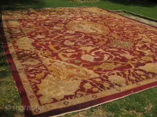 An old carpet 18 by 23 feet approximately, has been re-paired on multiple places.