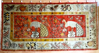 Xinjiang-Khotan rug with two peacocks in the central field surrounded by flowers.  The border is composed of several varieties of plants, flowers and.... butterflies.  One corner detail is rather odd,  ...