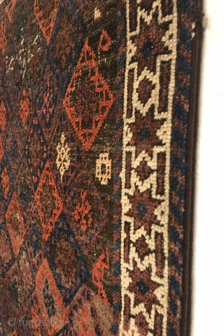 Antique Small Baluch Rug. 4th Quarter 19th Century. Northeast Persia. Rows of diamonds enclose a stepped cross containing birds head motifs. The white ground star border encloses a colorful and lively field  ...
