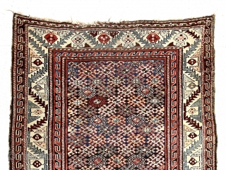 Antique tribal pile rug in good condition with some unusual design features. Possibly Veramin? Overall good medium length pile with very light wear. The dark blue field densely packed with latch hooked  ...