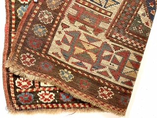 Antique Caucasian Kazak rug with interesting design features and a very unusual narrow size. The weaver altered an otherwise typical diagonal striped field with width and design changes. The extra wide ivory  ...