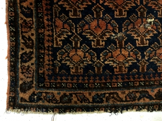 Antique blue ground Baluch bagface with an uncommon design featuring floral pendants usually associated with daktor e gazi prayer rugs. Overall good pile with a small center area of wear and two  ...