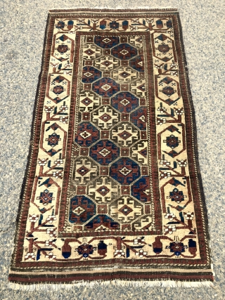 Antique Baluch rug with large scale Memling guls on a soft honey colored ground. Spaciously drawn older type border. Overall fair condition for an older piece with mostly good even pile. Moderately  ...