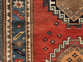 Antique small Kazak rug in good untouched condition with spacious drawing featuring charming large stylized humans. All natural colors including an attractive tomato red ground, sky blue border and an unusual lovely  ...