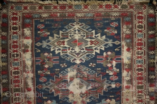A worn 19th century Shirvan rug with archaic large medallions. Foundation and loss to borders, an interesting example. 140x120cm