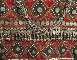 A very special child's vest from the Kohistan area of Pakistan. It is finely embroidered and extravagantly decorated with beads, buttons, and silver ornaments. There is a charming whistle on the front,  ...