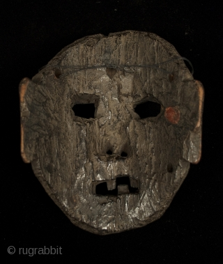 "Mask, Middle Hills, Nepal. 7"" (18 cm) high by 5.5"" (14 cm) wide. 18th century or earlier. A powerful piece with a little charred area near the right eye."