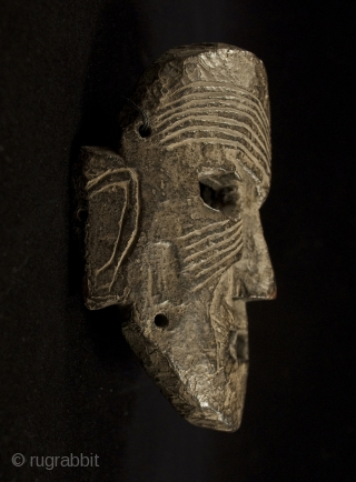 """Mask, Middle Hills, Nepal. 7"""" (18 cm) high by 5.5"""" (14 cm) wide. 18th century or earlier. A powerful piece with a little charred area near the right eye."""