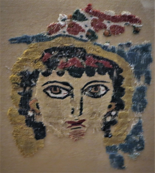 Fragment of Coptic woollen tapestry, probably a screen curtain, with the expressionistic head of a female figure, perhaps the personification of Spring. 3rd-4th c. 0.20x0.19 m. (ΓΕ 7177)Fragment of a linen tunic band, decorated with a grid pattern of lozenges and medallions with symmetrical motifs. From Egypt, 8th-9th c. 0.95x0.26 m. (ΓΕ 7173) Benaki Museum, Athens