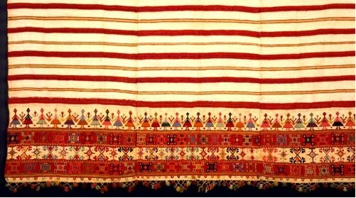 Woven bedspread ornamented with a dense geometric design and the representation of a group dance along the border. From Crete, 19th c. (ΕΕ 3167) image and text copyright Benaki Museum