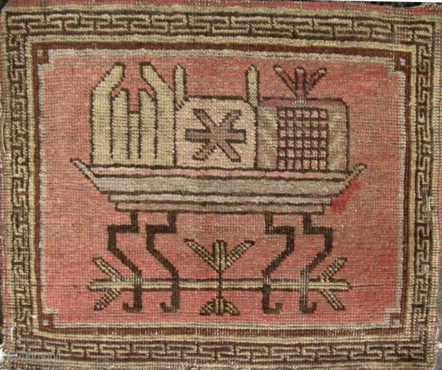 Xinjiang: Rare small sitting mat depicting an altar table with incense burner flanked by pomegranate and citron (Buddha's hand) and key fret border. Minor loss to bottom edge and small spot where  ...