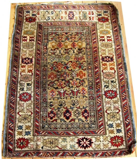 A  19th/20th Century Yellow Ground Shirvan (Kuba) Rug  Size 97 x 142 cm  With pastel coloured 'crab border', in fair overall condition with evenly worn pile, foundation warps are visible in  ...