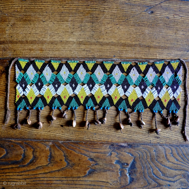 An early 20th century Cameroonian 'cache-sexe', with complex almost lace like 'offset' construction.Seed beads, cowrie shells and cotton string. Size 50 x 15cm.