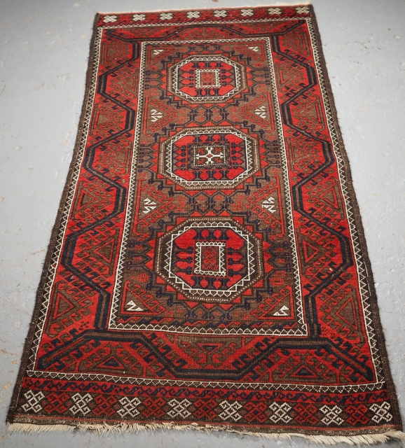 Antique Baluch tribal rug woven by the Salar Khani sub tribe. www.knightsantiques.co.uk  Size: 5ft 9in x 2ft 11in (174 x 89cm).  Circa 1900.  The rug has three large turreted guls on a soft brown  ...