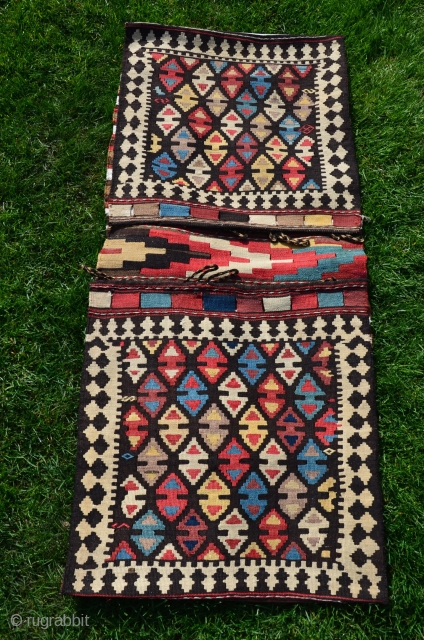 "Shahsavan flat woven (kilim) khorjin with decorated bridge. 1'10"" x 4'1"". Circa 1900. Wool. Some faded fuchsin in a few motifs testifies to age. Otherwise all saturated natural dyes. Clean and in  ..."