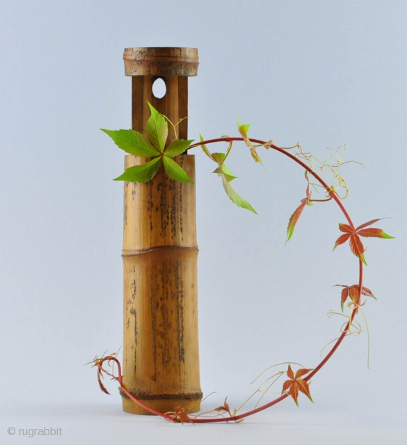 Japanese hanging vase (kakehanaire) of bamboo with an attractive dark texture and patina. Kakehanaire is a vase generally hung on a pillar of an alcove (tokonoma). Sometimes it is put on the  ...