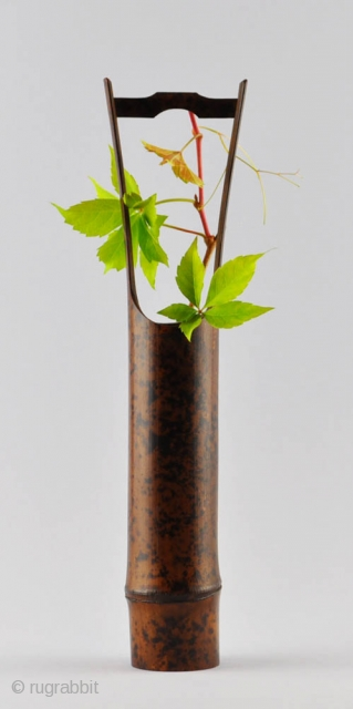 An elegant simple Japanese flower vase (hanaire) of dark bamboo with a natural design of black spots and an attractive patina. Unsigned.Probably first half of 20th century. 32x5 cm.