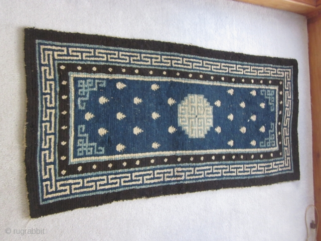 """Tibetan: Vintage khaden, 2'3"""" by 4'6"""", with latch hook central medallion in light blue and frog's feet on a saturated indigo ground, before 1900. Some scattered re-piling."""