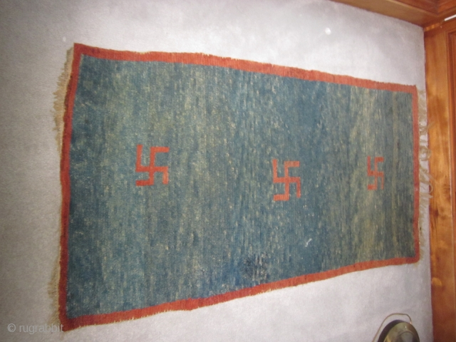 "Tibetan khaden, pre-1900, 2'5"" by 4'6"", three eccentric swastikas on an abrashed blue ground, some quality repiling in field"